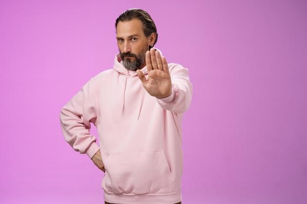 Stań tam. portret poważnie wyglądający, apodyktyczny dorosły, brodaty ojciec wyciąga rękę i zatrzymuje tabu bez gestu zabraniającego przyjścia na imprezę, solidny, pewny siebie, wymagający rzucenia palenia, stojący na fioletowym tle.