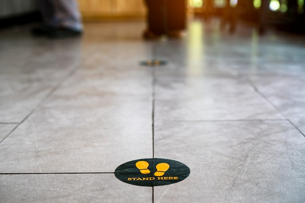 Stań tutaj znak lub symbol stopy na podłodze w kawiarni