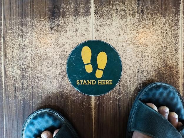 Stań tutaj znak stopy lub symbol na podłodze