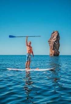 Stand up paddle boarding sportowiec pozuje na desce sup przygoda morza z niebieską wodą