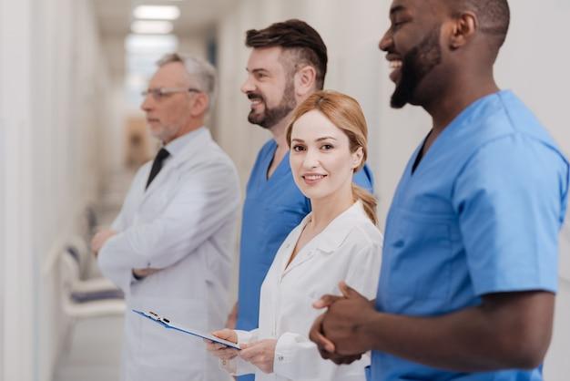 Stanie się częścią zespołu. urocza młoda praktykantka ciesząca się procesem egzaminacyjnym z kolegami i stojąca z teczką w rękach w klinice, wyrażając swoje szczęście
