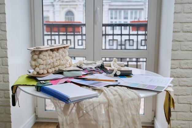 Stanowisko projektanta tkanin, na paletach biurka z tkaninami