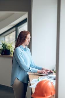 Stanowisko. skoncentrowana zaangażowana długowłosa kobieta pracująca na laptopie stojąca przy oknie w pomieszczeniu w świetle dziennym