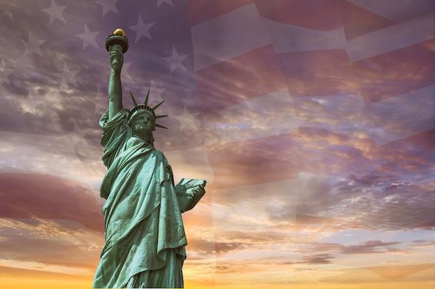 Stany zjednoczone ameryki w statui wolności na tle flagi usa zachód słońca