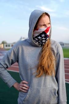 Stany zjednoczone fan futbolu amerykańskiego, patrząc gdzieś ze złością. rudzielec kobieta z wiązanym na twarzy usa flaga barwi bandana złości spojrzenie