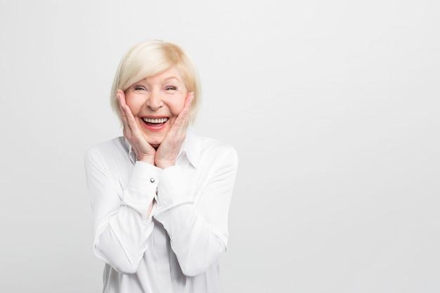 Stara, ale szczęśliwa kobieta nosi białą bluzkę i pokazuje, że jest bardzo zaskoczona. ma powodzenia.