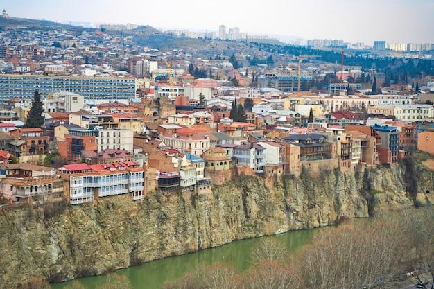 Stara architektura tbilisi. gęsta zabudowa budynku mieszkalnego na klifie nad rzeką.