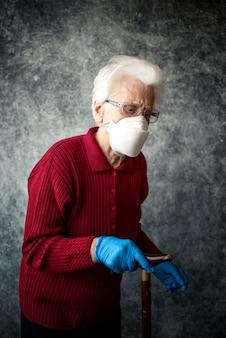 Stara babcia chroni się przed zakażeniem koronawirusem za pomocą rękawiczek medycznych i maski oddechowej