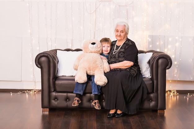 Stara babcia z wnukiem siedzi na kanapie.