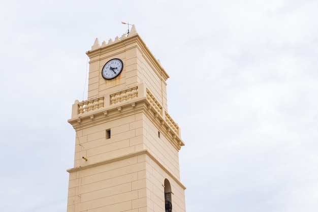 Stara beżowa wieża zegara na niebie.