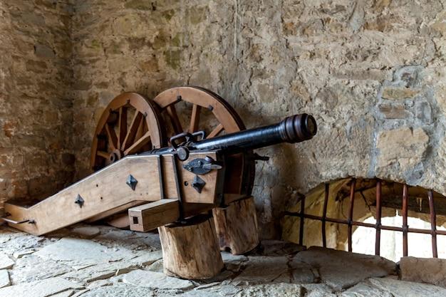 Stara broń z drewnianymi kołami na tle ceglanego muru twierdzy.