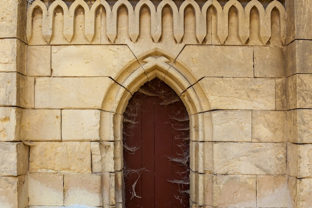 Stara ceglana fasada z drewnianymi drzwiami kościoła i dekoracjami figuralnymi.