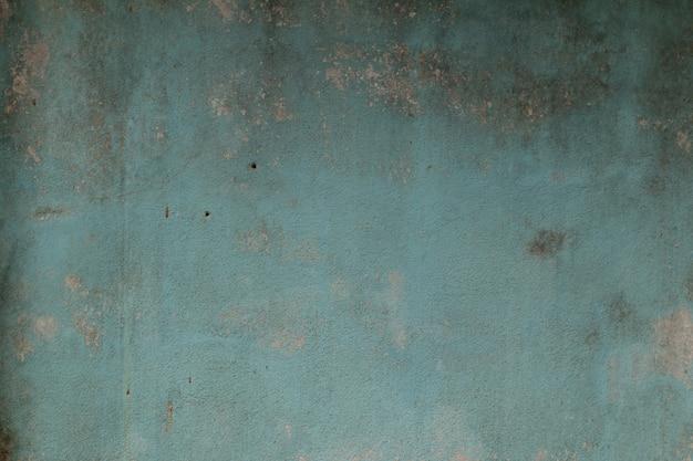 Stara cement ściana maluje błękitnego koloru abstrakta tło.