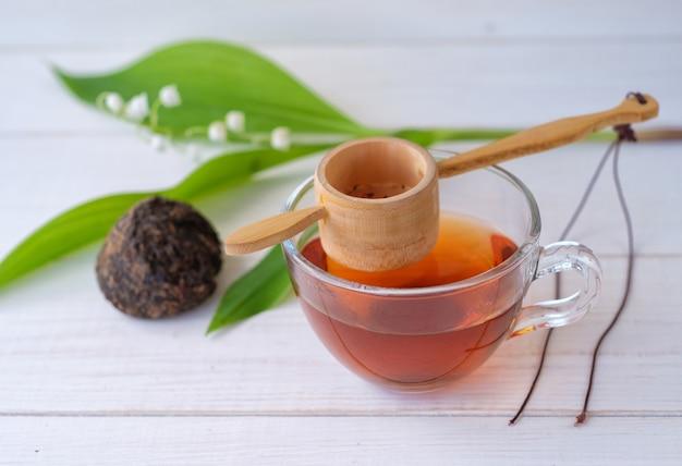 Stara chińska herbata shen puer w formie gniazda, parzona herbata w szklanej filiżance i kwiat srebrnej konwalii na białym drewnianym stole