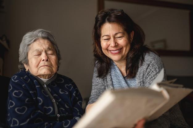 Stara chora kobieta z utratą pamięci. uśmiechnięta córka pokazuje album fotograficzny.