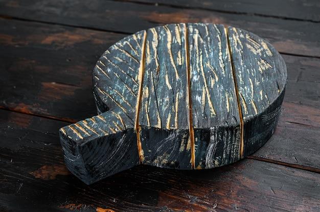 Stara ciemna deska do krojenia na brązowy drewniany stół. ciemne tło. widok z góry. skopiuj miejsce.
