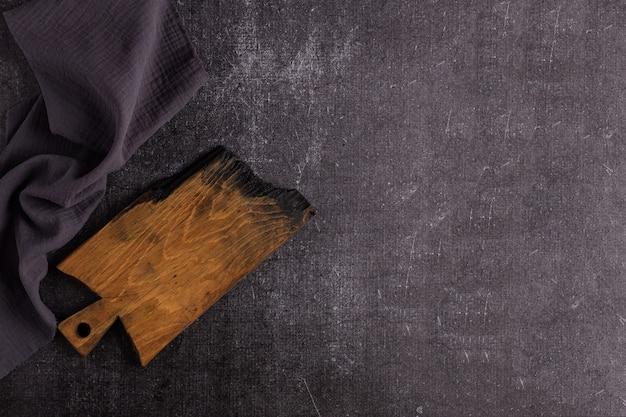 Stara ciemna deska do krojenia na ciemnym tle. deska jest zwęglona