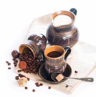 Stara czarna ceramika, ziarna kawy, słodycze i kubek napoju
