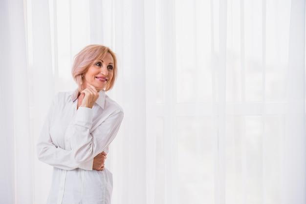 Stara dama z krótkim włosy patrzeje szczęśliwy z kopii przestrzenią