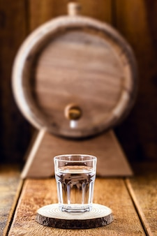 Stara dębowa beczka i kieliszek wysokiej jakości alkoholu destylowanego
