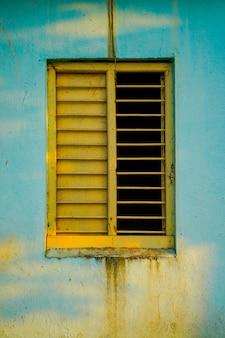 Stara dom ściana z żółtym drewnianym okno
