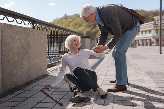 Stara dość wesoła kobieta leży na ziemi i uśmiecha się, podczas gdy uprzejmy mąż jej pomaga