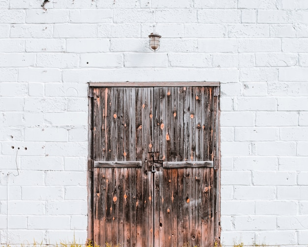 Stara drewniana brama w białym murem
