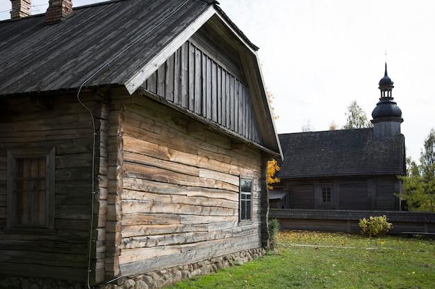Stara drewniana chata w stylu rustykalnym. w tle rustykalny drewniany kościół. zdjęcie wysokiej jakości