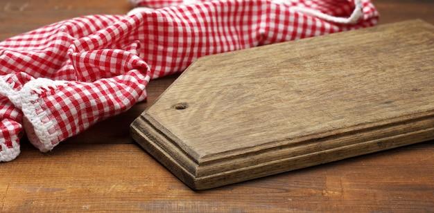 Stara drewniana deska do krojenia i złożona czerwono-biała bawełniana serwetka kuchenna na drewnianym brązowym tle, widok z góry