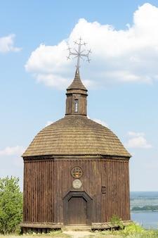 Stara drewniana kaplica pod błękitne niebo z chmurami w vitachov na ukrainie. park narodowy horodyshche novgorod-svyatopolche. zabytek historyczny