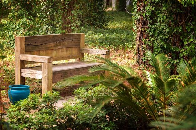 Stara drewniana ławka zepsuta przez wiatr i deszcz stoi w parku miejskim