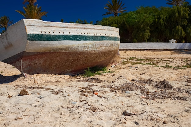 Stara drewniana łódź na białym piasku wybrzeża morza śródziemnego