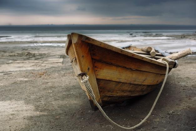 Stara drewniana łódź rybacka na brzegu. na tle zachmurzonego nieba.