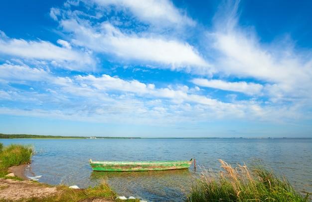Stara drewniana łódź rybacka na letnim brzegu jeziora (świtiaź, ukraina)