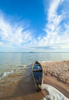 Stara drewniana łódź rybacka powodzi w pobliżu brzegu jeziora i letniego nieba za (świtiaź, ukraina)