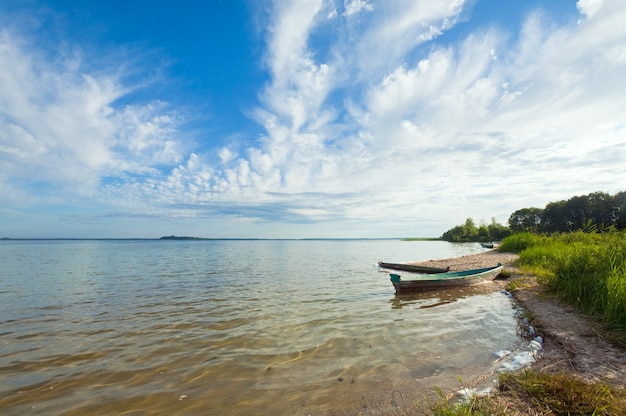 Stara drewniana łódź rybacka w pobliżu brzegu jeziora i letniego nieba za (świtiaź, ukraina)