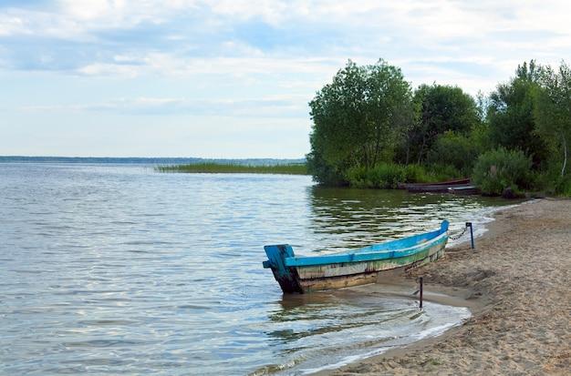 Stara drewniana łódź rybacka w pobliżu letniego brzegu jeziora (świtiaź, ukraina)