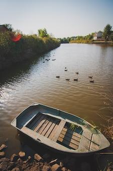 Stara drewniana łódź w jeziorze. na jeziorze płynie romantyczna łódź.
