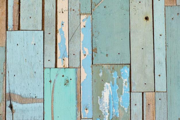 Stara drewniana powierzchnia, zielona, niebieska, pięknie zdobiona na tle ściany