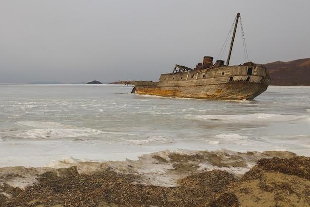 Stara drewniana radziecka łódź wielorybnicza osiadła na mieliźnie na brzegu zatoki