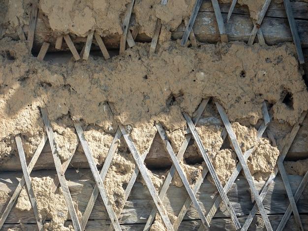 Stara drewniana ściana pokryta jest gliną i słomą