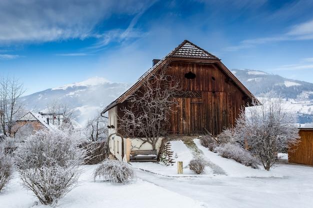Stara drewniana stodoła pokryta śniegiem w austriackich alpach