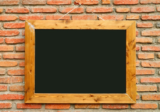 Stara drewniana tablica z ramą na postarzanej ścianie z cegły