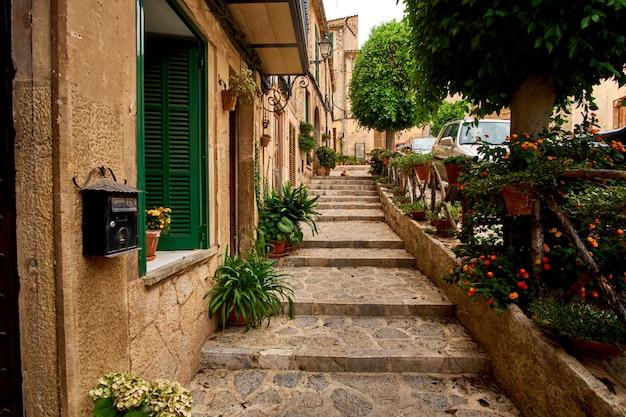 Stara europejska ulica ozdobiona świeżymi kwiatami miasta valldemossa. palma de mallorca. hiszpania.
