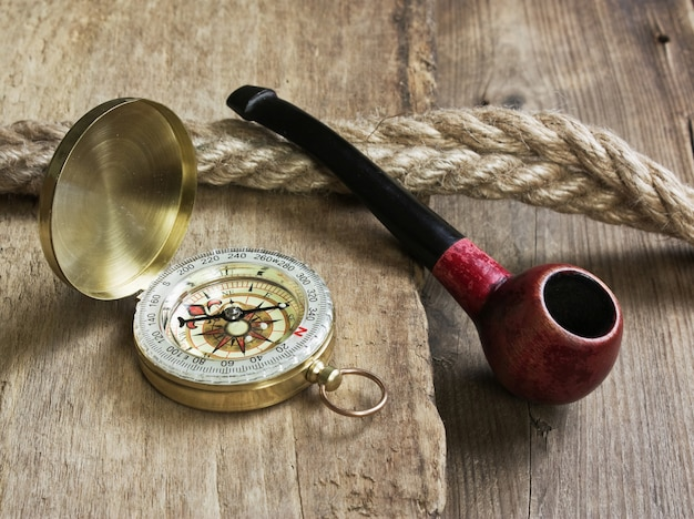 Stara fajka tytoniowa i kompas na drewnianym tle