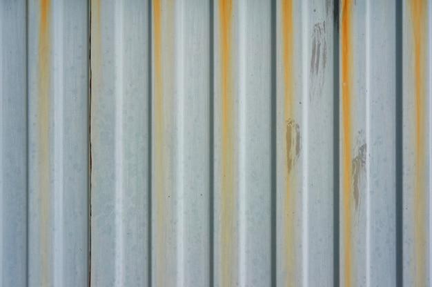 Stara falista metalowa ściana z zardzewiałymi smugami.