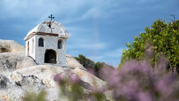 Stara i mała kapliczka położona na skałach w pobliżu wybrzeża morza egejskiego, dookoła krzaki, zachmurzone niebo, grecja
