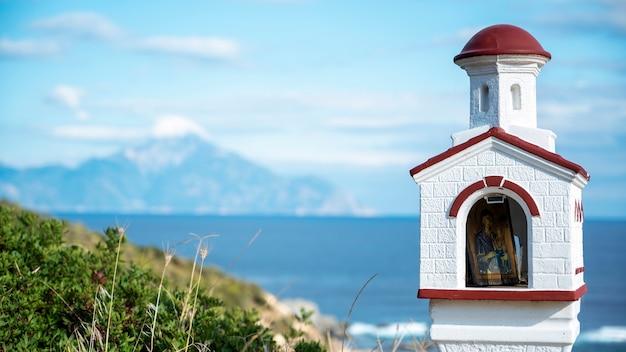 Stara i mała kapliczka położona na skałach w pobliżu wybrzeża morza egejskiego, wokół krzaków, wody i gór, grecja
