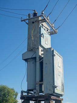 Stara i zardzewiała stacja transformatorowa latem w pogodny dzień na tle błękitnego nieba z bliska