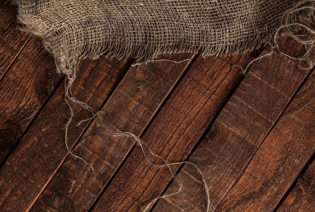 Stara jutowa tekstura na drewnianym stołowym tle
